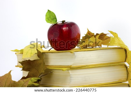 red apple with a green leaf on a stack of books around the fallen yellow leaves - stock photo