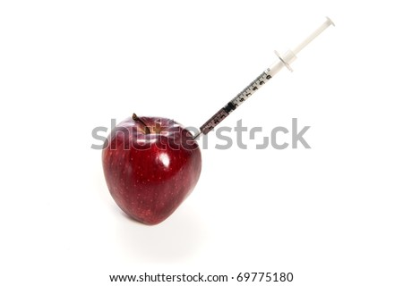 Red apple with a hypodermic needle/syringe in it isolate on white - stock photo