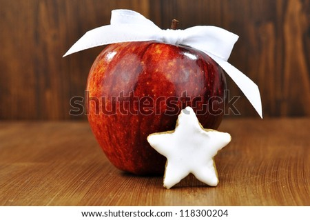 Red apple with a white bow and biscuit with cinnamon