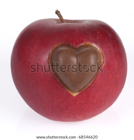 Red apple with carved heart and a chocolate - stock photo