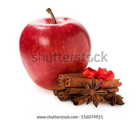 red apple with cinnamon and star anise isolated on white