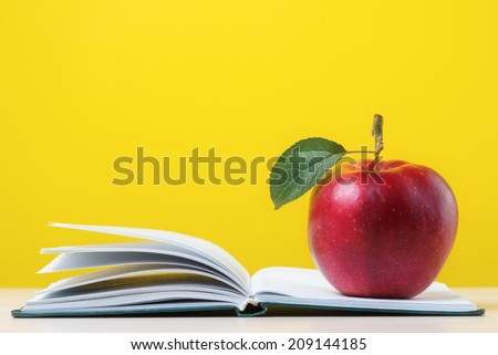 Red apple with green leaf on open notebook - stock photo
