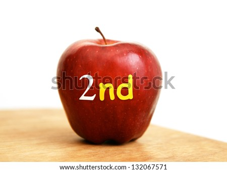 "Red Apple with ""2nd"" letters Representing Second Grade, Sitting on a Teachers' Desk. Isolated on White. - stock photo"