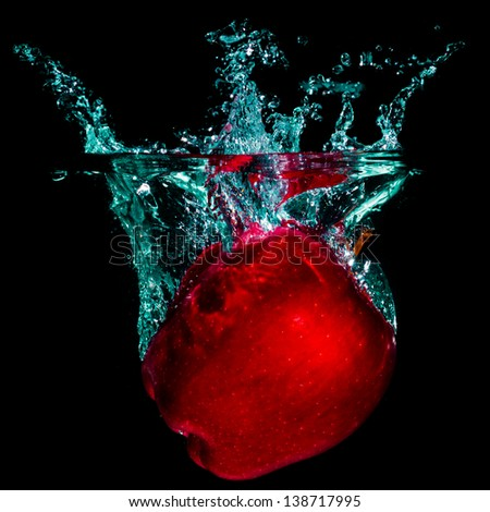 Red apple with splashing water on a black background - stock photo