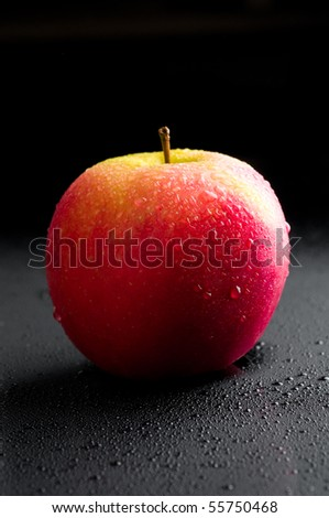 Red apple with water drops over black - stock photo