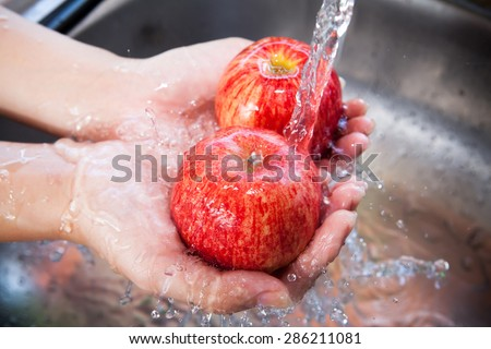 Red apple with water splash on hands, Fresh an Healthy foods concept - stock photo