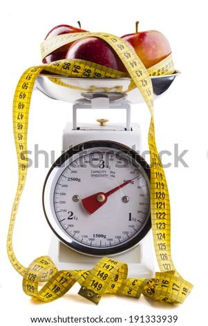 Red apple with  yellow measuring tape on kitchen scale isolated on white - stock photo