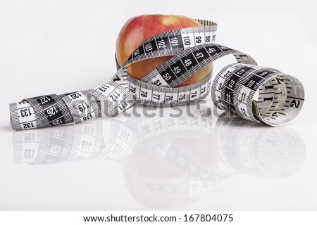 Red apple wrapped in measurement tape on white with reflection - stock photo