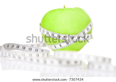 Red apple wrapped with tape measure, close-up
