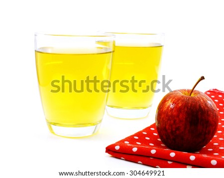 red apples and glass of fresh apple juice over white background