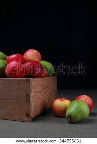 Red apples and green pears in wooden box on a black bakcground