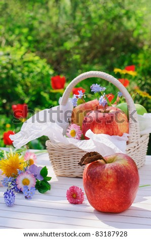 Red apples, flowers and basket on white garden table - stock photo