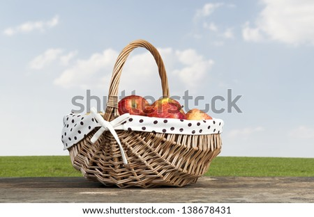 red apples in a basket, sky with clouds as background