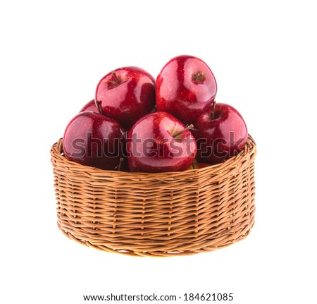 Red apples in a wicker basket, isolated on white background.