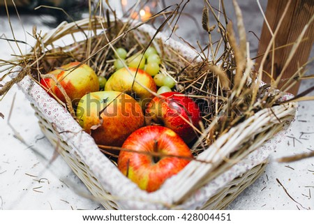 Red apples in a wicker basket with straw. Picnic in the forest - stock photo