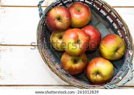 Red apples in basket on white wooden background - stock photo