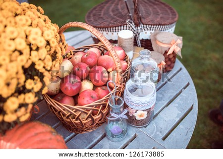 Red apples in basket, yellow flowers and basket on garden table - stock photo