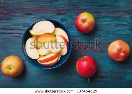 Red apples with slices over blue wooden background - stock photo