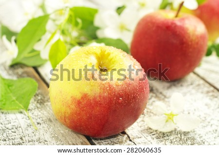 Red apples with white flowers on the wooden surface