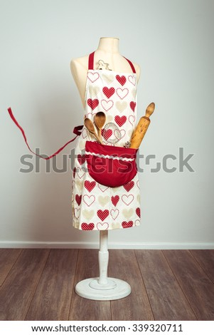 Red apron with pocket filled with utensils - stock photo