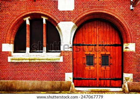 Red arch wooden door and window of a red brick classical building, Europe. Architectural theme. Photo in retro style. Paper texture. Aged textured photo in retro  - stock photo