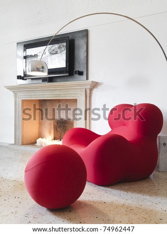red armchair and lamp near a a fireplace - stock photo