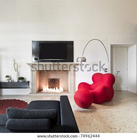 red armchair near a fireplace - stock photo