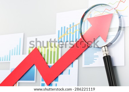 Red arrow and magnifying glass on the background of graphs and charts. Looking upside growth arrow with magnifying glass. Graphs and data confirming growth.  - stock photo