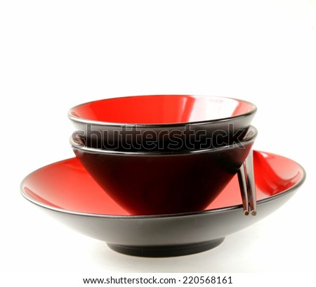 Red asian style tableware bowls with chopsticks - stock photo