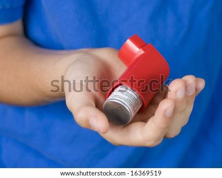 Red Asthma Inhaler in Boys hand - stock photo