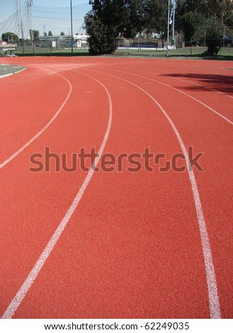 Red athletic running track with lines