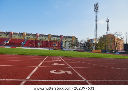 Red athletic track treadmill at the stadium with the numbering. - stock photo