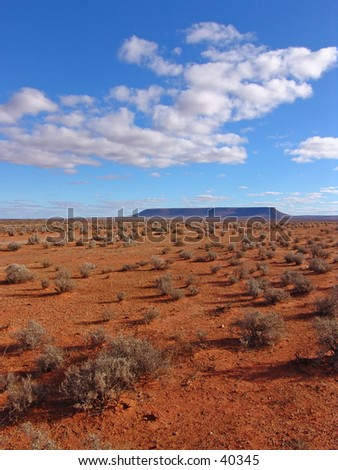 Red australia desert with a distant mountain - stock photo