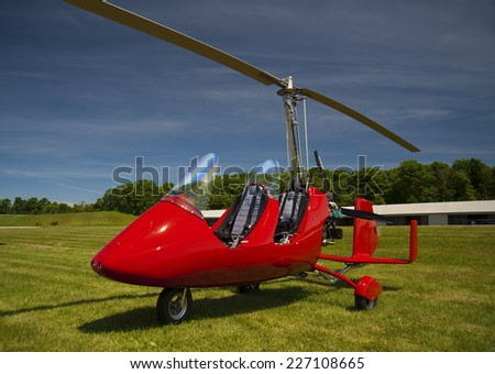 Red autogyro parked at the airfield in sunny day - stock photo