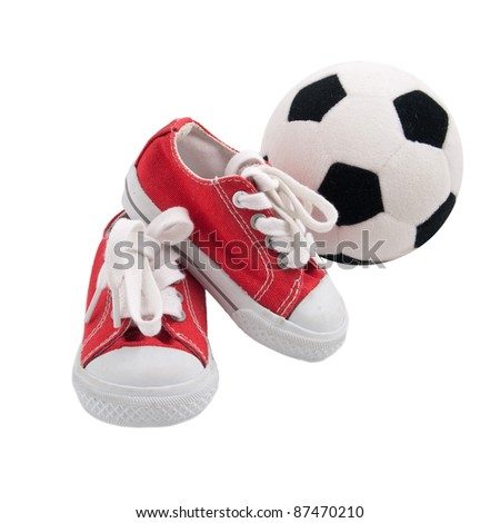 Red baby sneakers with a ball isolated on white background