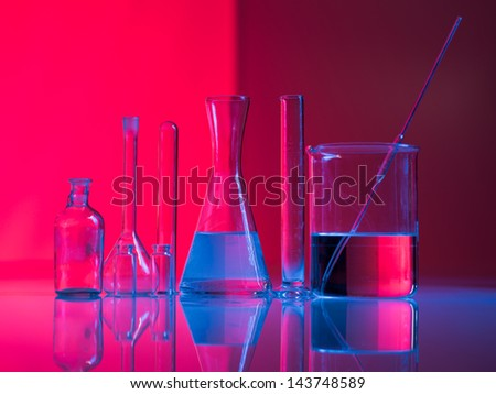 Red background with experimental glass containers and their reflection on a table in a blue light - stock photo