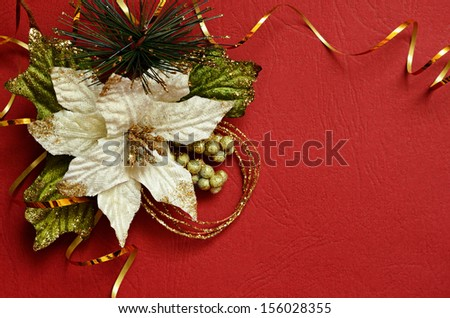 Red background with poinsettia and golden streamer in a corner - stock photo