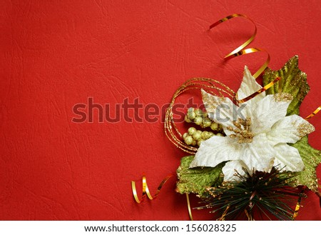 Red background with white poinsettia and golden streamer in a corner - stock photo