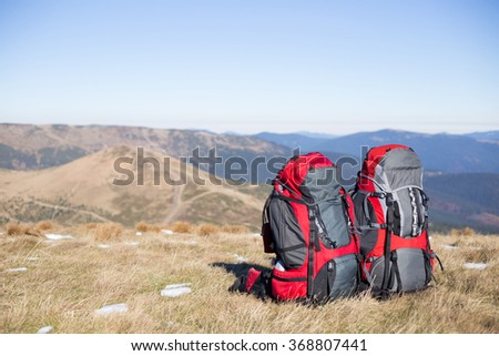 Red backpack standing on top of the mountain. - stock photo