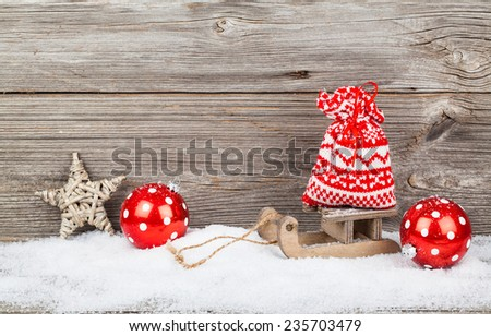 red bag on old rustic wooden sledge, over wooden background - stock photo