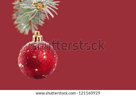 Red ball hanging on Christmas tree over red background with copy space. - stock photo