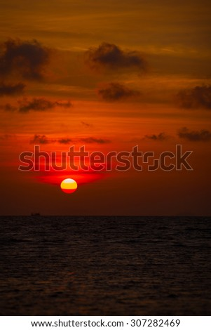 Red ball of the sun, setting slowly against the distant, hazy horizon, over a tropical sea. - stock photo