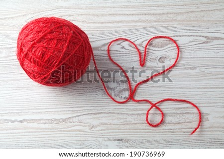 red ball of wool on wooden table background - stock photo