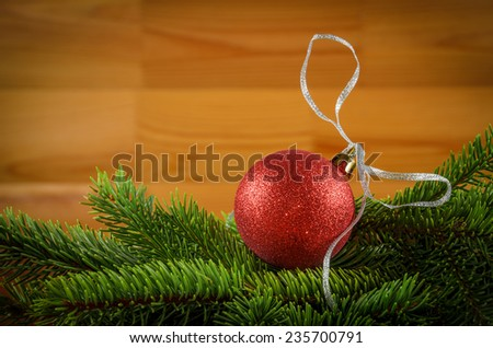 red ball with silver ribbon on the green christmas tree branches - stock photo