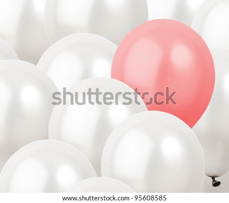 red balloon in between white balloons