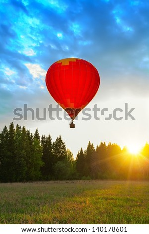 Red balloon in sun beams - stock photo