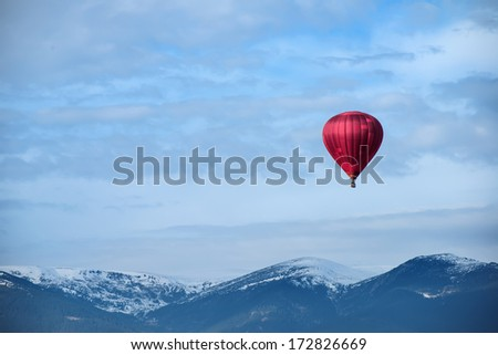 Red balloon in the blue cloudy sky - stock photo