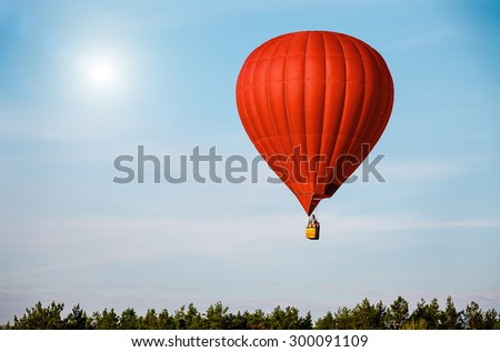 Red balloon in the blue sky wuth forest in the down - stock photo