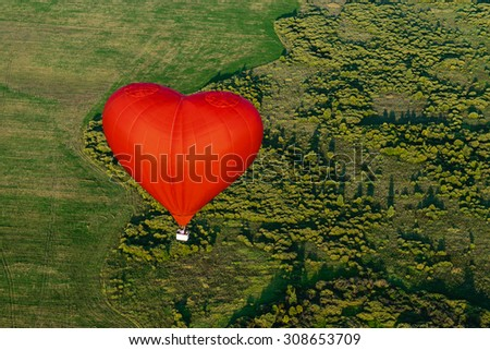 Red balloon in the form of heart over green fields and forests - stock photo