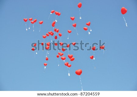 Red balloons with the messages in the blue sky - stock photo